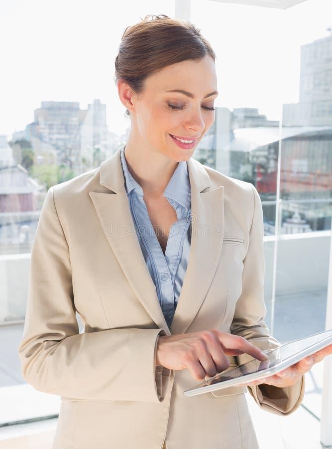 Donna di affari sorridente che per mezzo del suo pc della compressa immagine stock libera da diritti