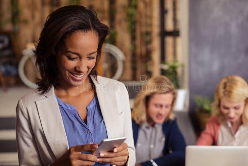 Donna di affari sorridente che per mezzo di uno smartphone fotografia stock libera da diritti