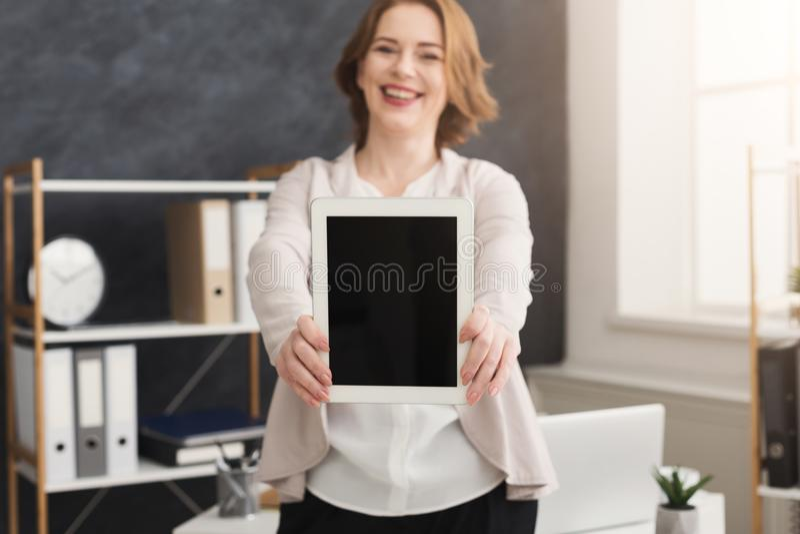 Donna di affari sorridente che presenta lo schermo della compressa fotografia stock libera da diritti
