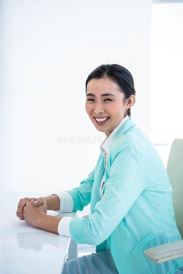 Donna di affari sorridente che si siede sulla sua sedia fotografie stock libere da diritti