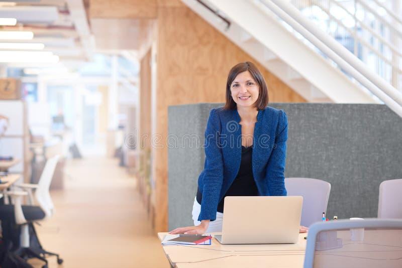 Donna di affari sorridente che sta al suo scrittorio in offi moderno luminoso fotografia stock