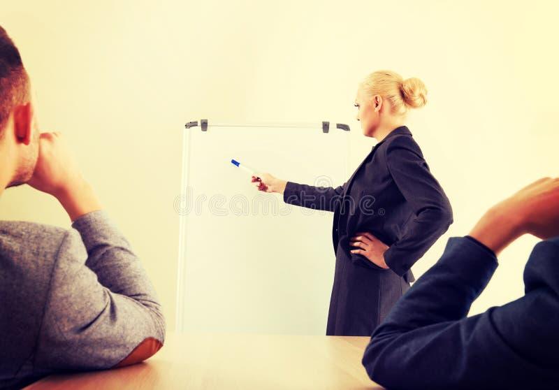 Donna di affari sorridente che traccia un grafico per i suoi colleghi sulla lavagna fotografia stock libera da diritti