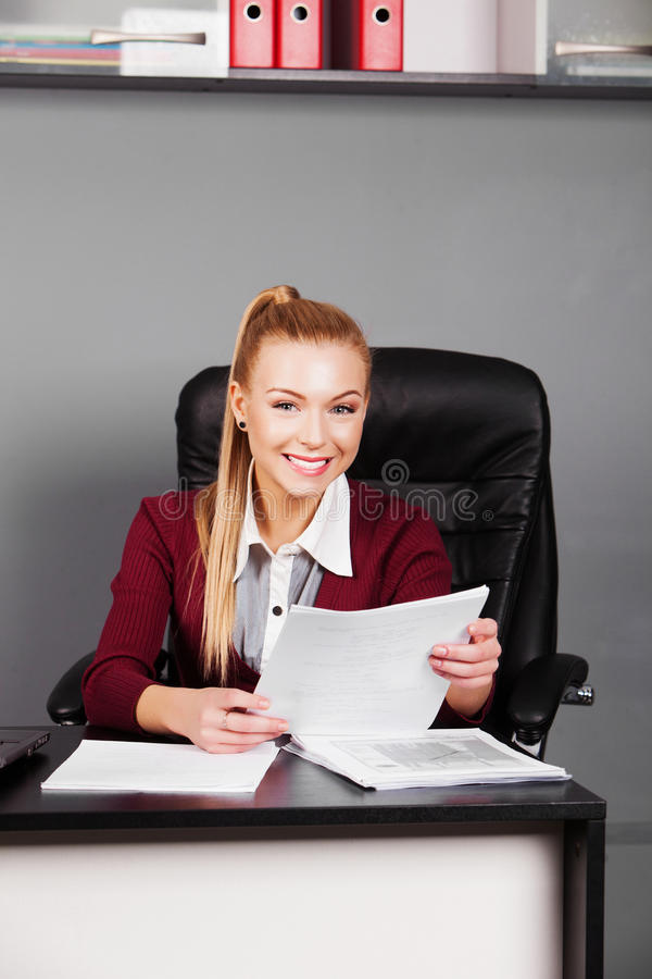 Donna di affari sorridente con carta in ufficio fotografia stock libera da diritti