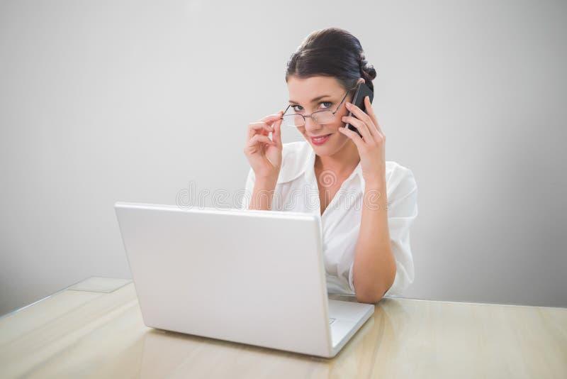 Donna di affari sorridente con la telefonata di classe di vetro fotografie stock