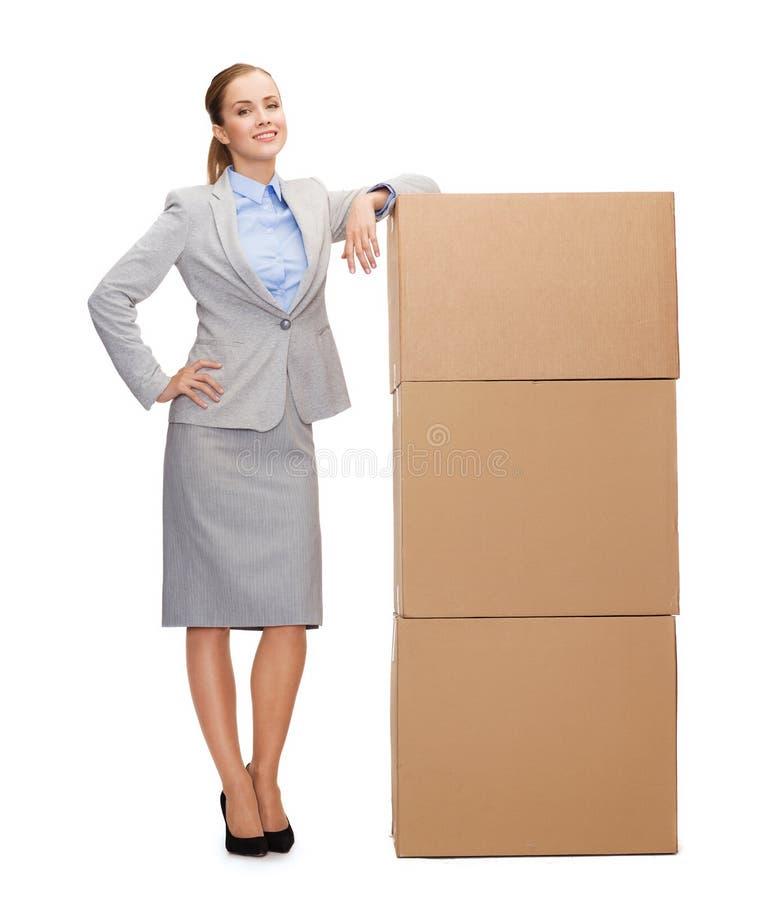 Donna di affari sorridente con le scatole di cartone fotografia stock