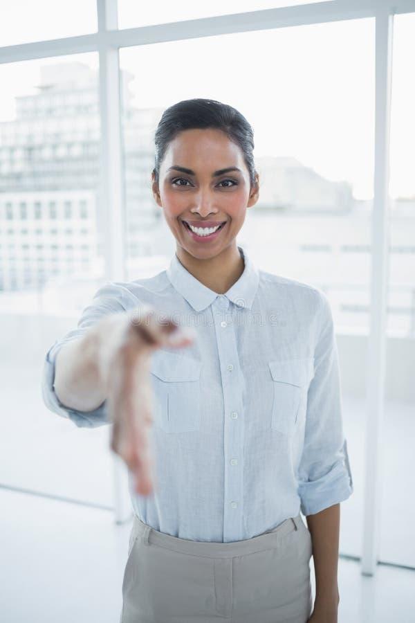 Donna di affari sorridente contenta che raggiunge la sua mano fotografie stock libere da diritti