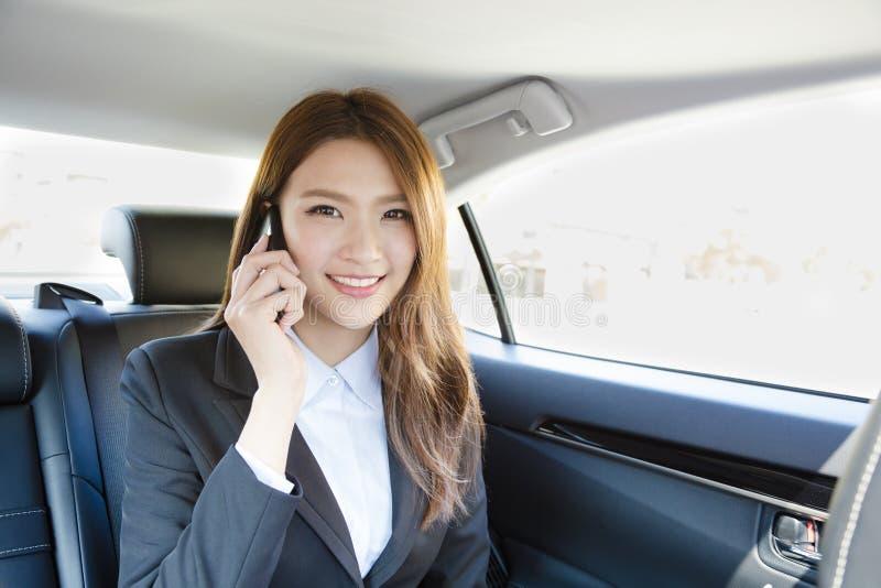 Donna di affari sorridente dentro la sua automobile che parla sul telefono cellulare fotografia stock