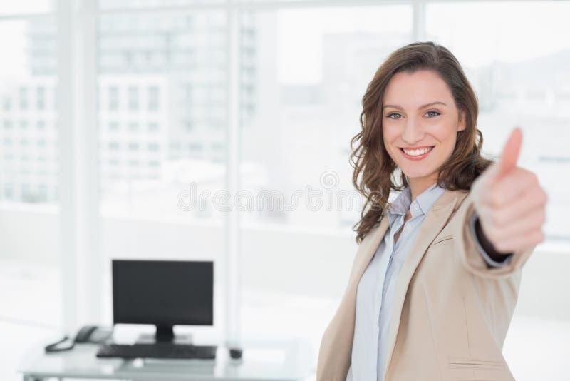 Donna di affari sorridente elegante che gesturing i pollici su in ufficio fotografie stock libere da diritti