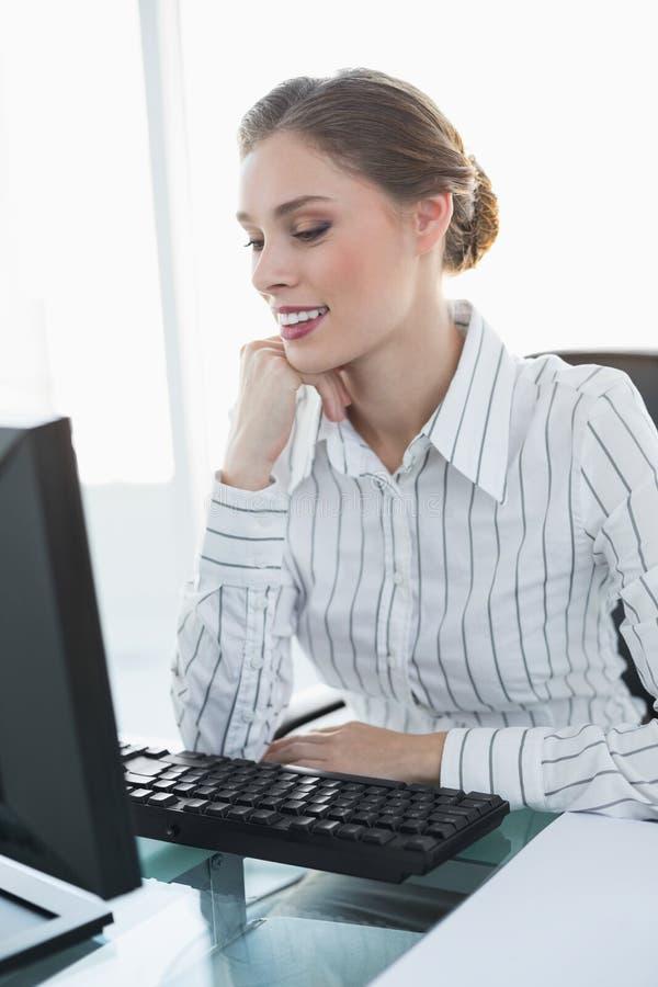 Donna di affari sorridente elegante che si siede al suo scrittorio immagini stock libere da diritti