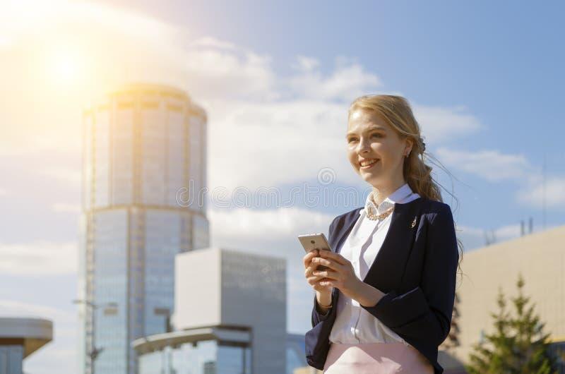 Donna di affari sorridente felice che riceve buone notizie nel messaggio Via di camminata di signora di affari durante la pausa immagini stock