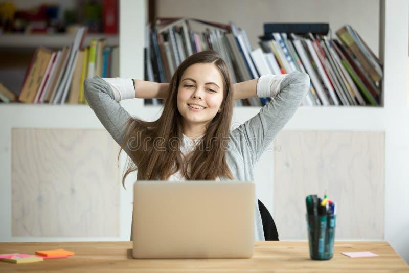 Donna di affari sorridente felice che si rilassa allo scrittorio del lavoro in offi moderno fotografia stock libera da diritti