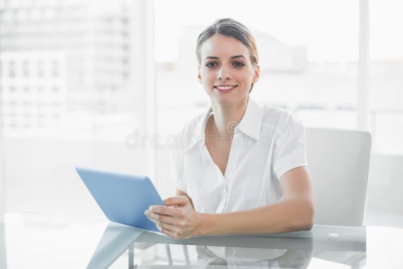 Donna di affari sorridente giuliva che lavora con la sua compressa che esamina macchina fotografica immagini stock libere da diritti