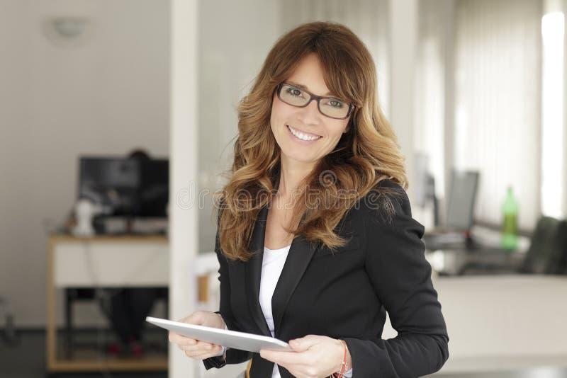 Donna di affari sorridente in ufficio immagini stock