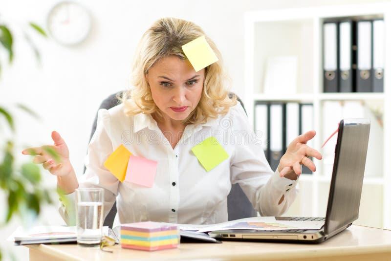 Donna di affari sovraccarica che lavora nell'ufficio e che esamina le note di ricordo degli autoadesivi fotografia stock libera da diritti
