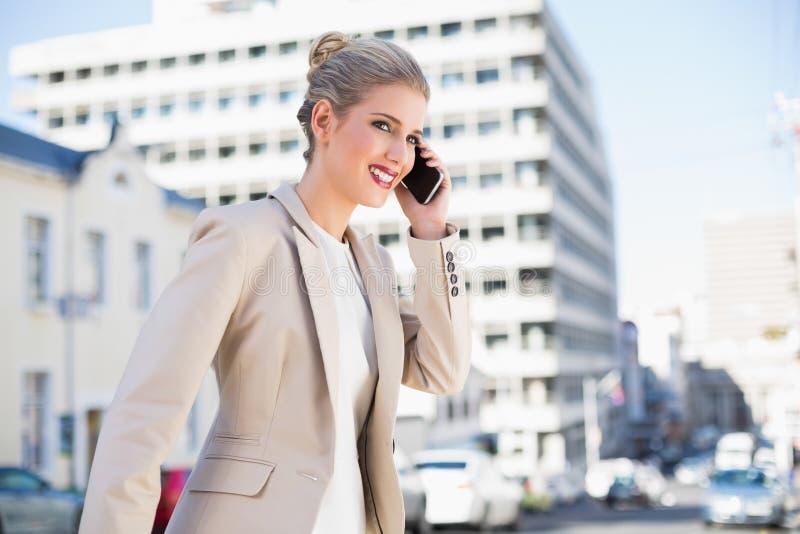 Donna di affari splendida allegra che ha una telefonata fotografia stock