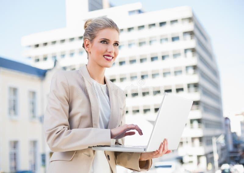 Donna di affari splendida allegra che lavora al computer portatile fotografia stock