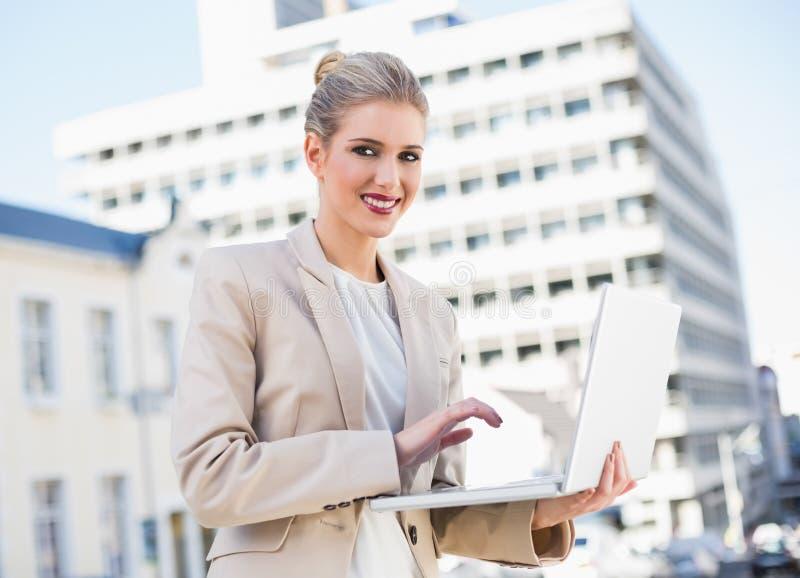 Donna di affari splendida felice che lavora al computer portatile fotografia stock