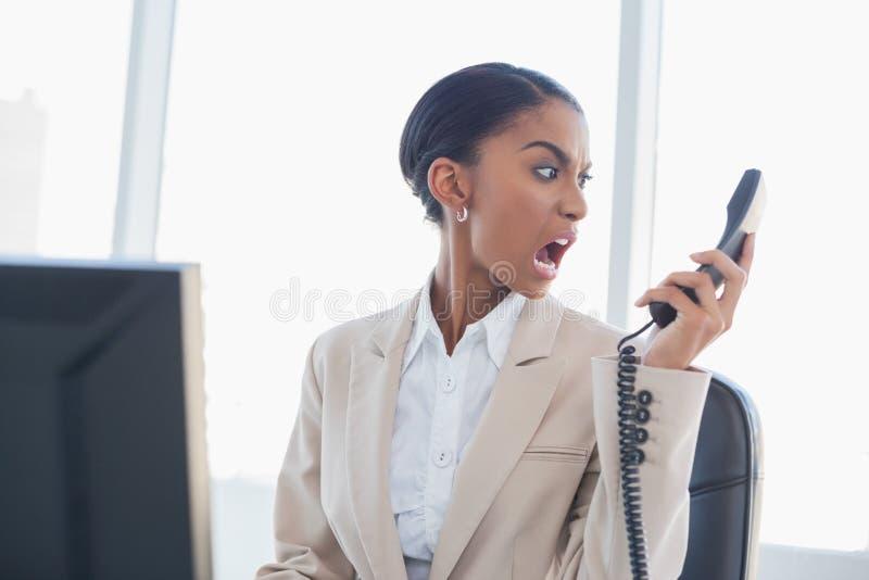 Donna di affari splendida furiosa che grida sul telefono fotografie stock