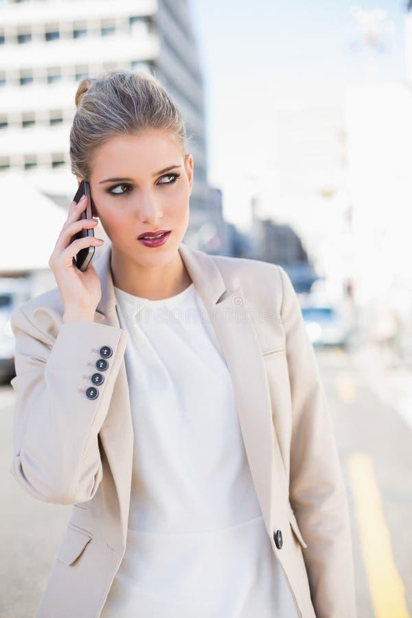 Donna di affari splendida pensierosa che ha una telefonata fotografia stock