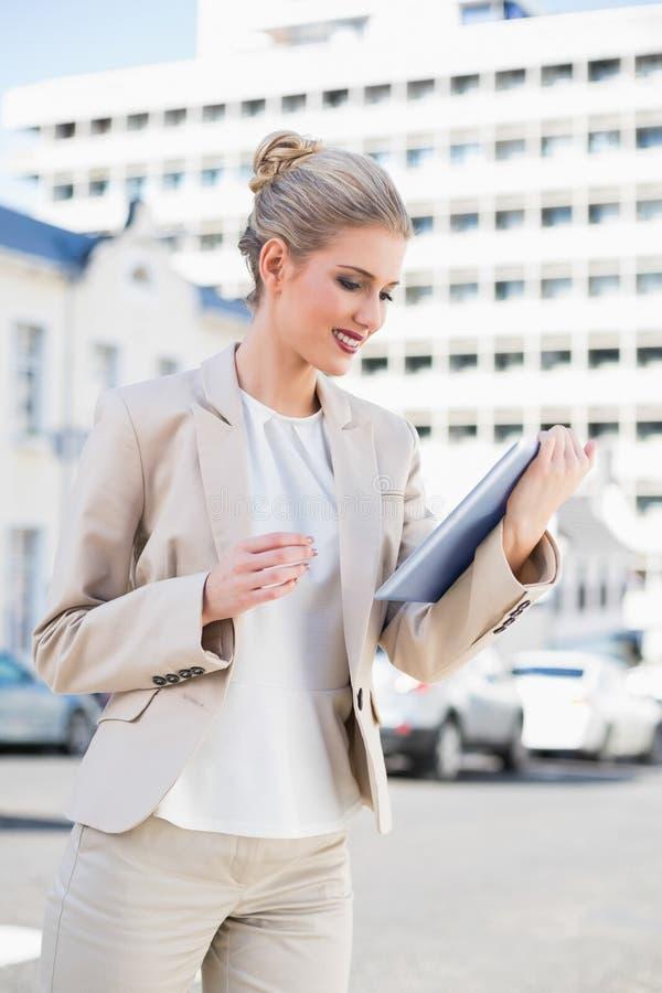 Donna di affari splendida sorridente che per mezzo del pc della compressa immagini stock libere da diritti