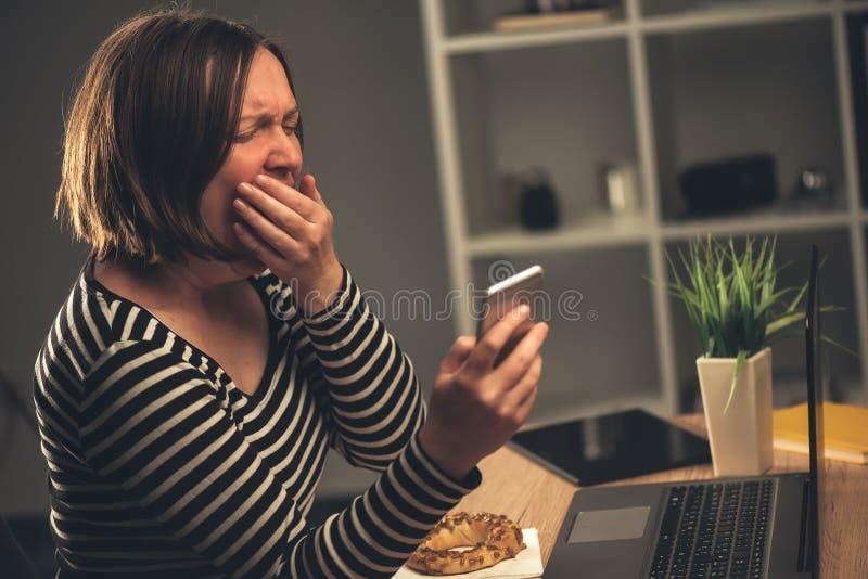 Donna di affari stanca che lavora fuori orario e che sbadiglia nell'ufficio fotografie stock libere da diritti