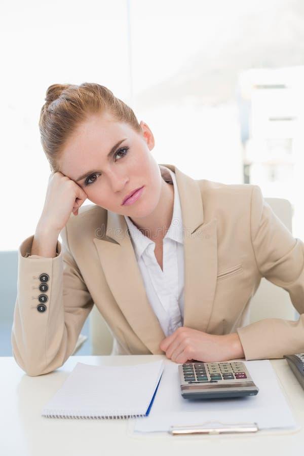 Donna di affari stanca che si siede alla scrivania fotografia stock