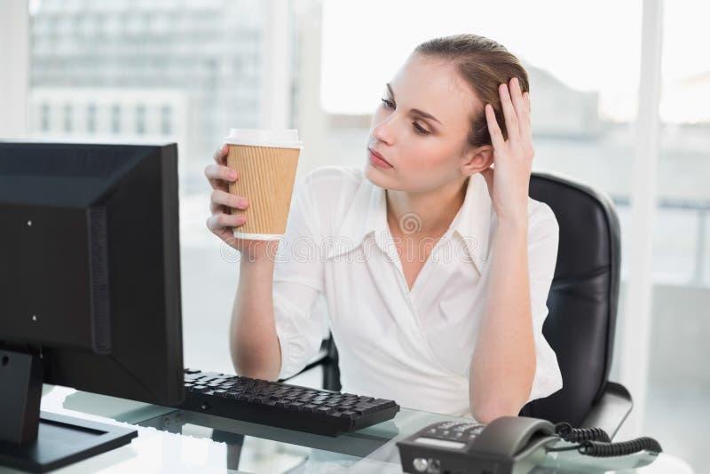 Donna di affari stanca che tiene tazza eliminabile che si siede allo scrittorio fotografie stock libere da diritti
