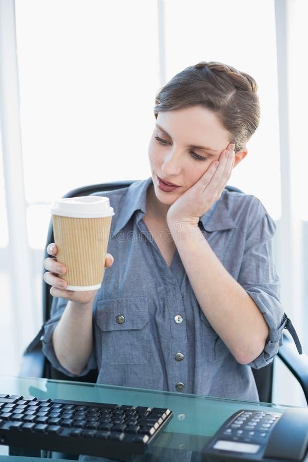 Donna di affari stanca che tiene una tazza eliminabile fotografie stock libere da diritti