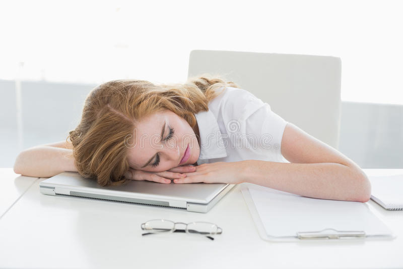Donna di affari stanca con la testa sul computer portatile in ufficio fotografia stock