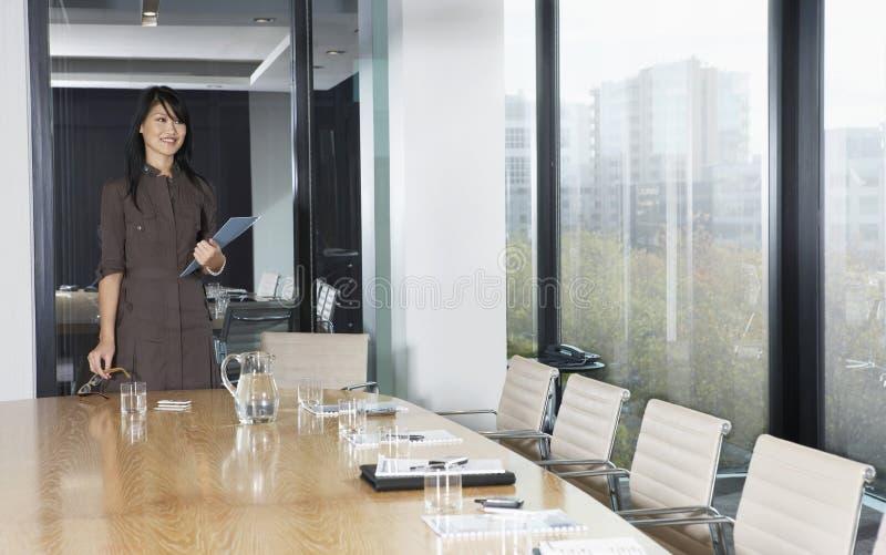 Donna di affari Standing At Table in sala del consiglio fotografie stock libere da diritti