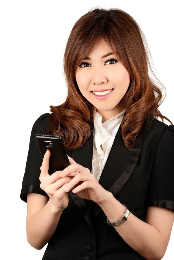 Donna di affari su funzionamento del cellulare mentre parlando sullo smartphone fotografie stock