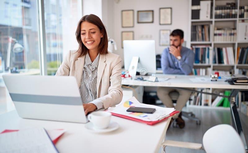 Donna di affari sul lavoro che lavora e che esamina schermo di computer nell'ufficio fotografia stock