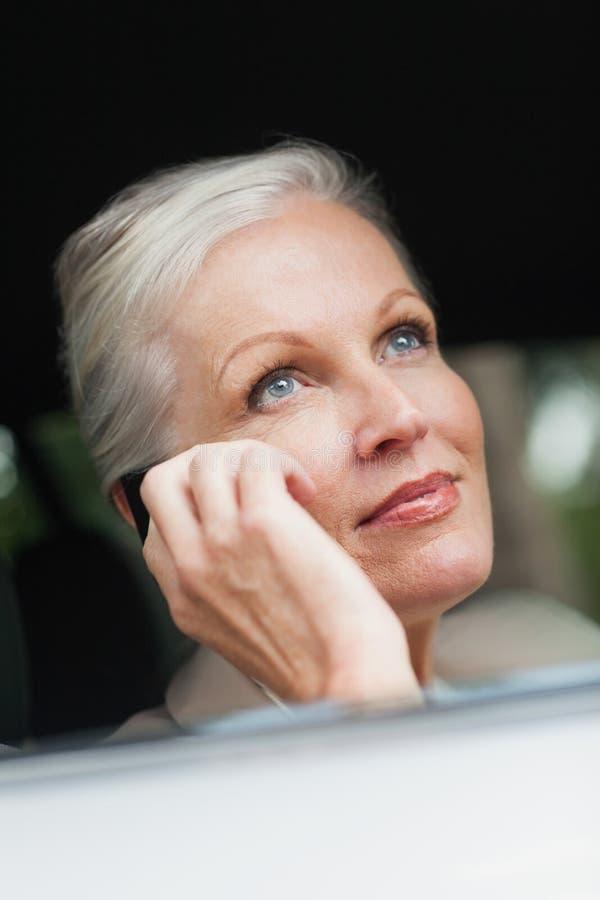 Donna di affari sul telefono che conduce automobile di classe fotografia stock libera da diritti