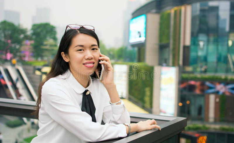 Donna di affari sul telefono nell'ambiente moderno immagine stock