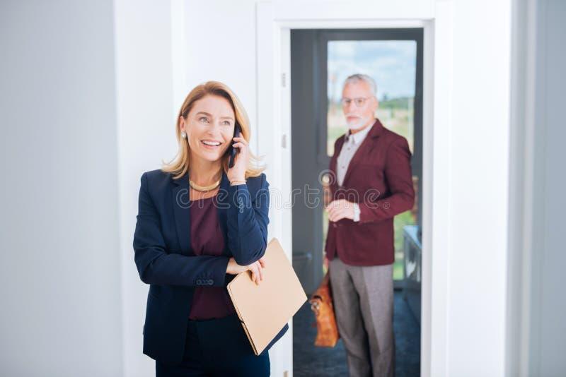 Donna di affari supplichevole d'orientamento che indossa gli accessori alla moda che ricevono le chiamate fotografie stock libere da diritti