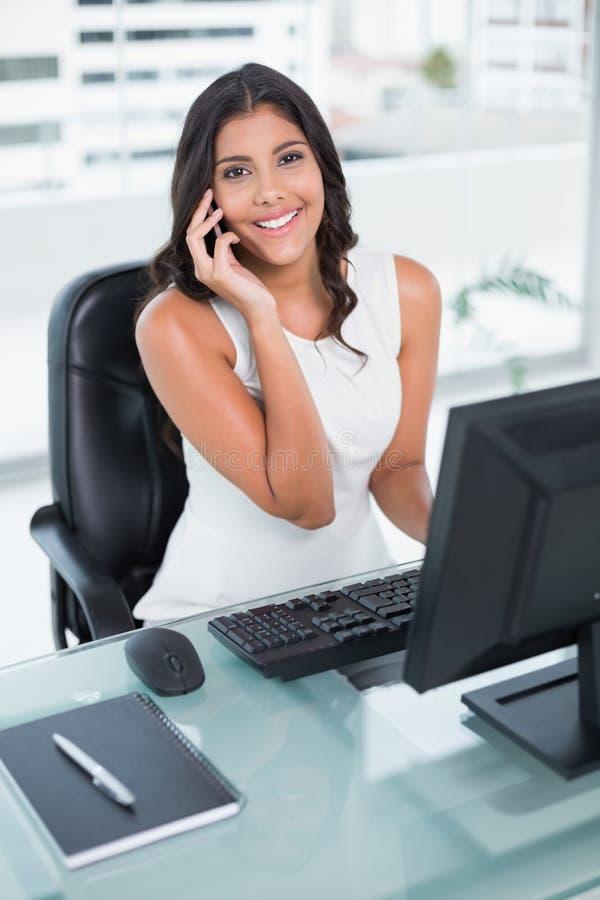 Donna di affari sveglia allegra che telefona sullo smartphone immagine stock