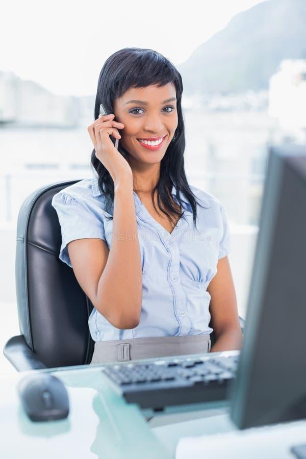 Donna di affari sveglia che chiama qualcuno con il suo telefono cellulare fotografia stock libera da diritti