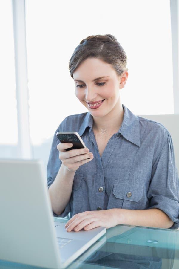 Donna di affari sveglia che per mezzo del suo smartphone che si siede al suo scrittorio immagine stock