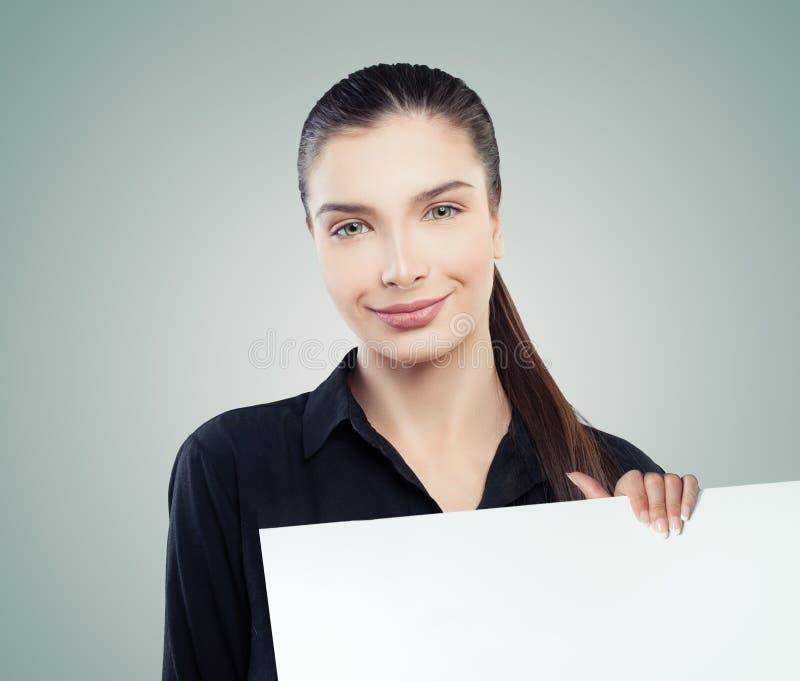 Donna di affari sveglia che tiene il fondo vuoto bianco del cartone con lo spazio della copia per la pubblicità introduzione sul  fotografia stock libera da diritti