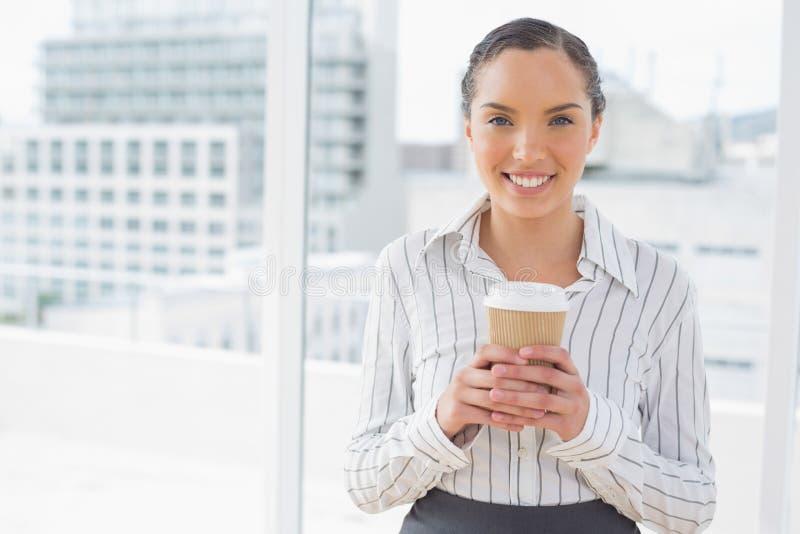 Donna di affari sveglia che tiene un caffè fotografia stock