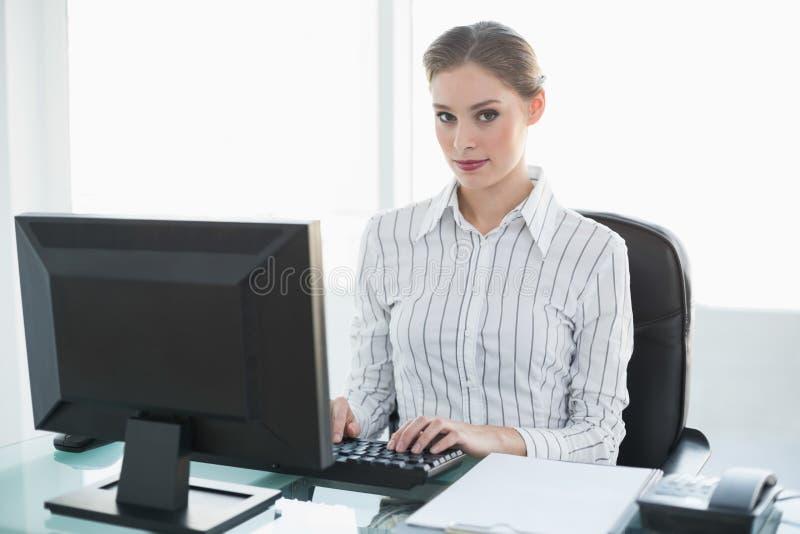 Donna di affari sveglia concentrata che lavora al suo computer mentre sedendosi al suo scrittorio fotografie stock