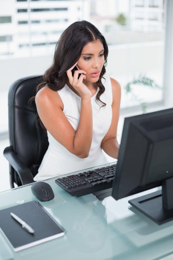 Donna di affari sveglia seria che telefona sullo smartphone fotografia stock libera da diritti