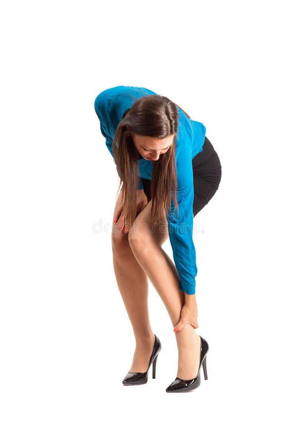 Donna di affari in tacchi alti che toccano la sua caviglia immagine stock