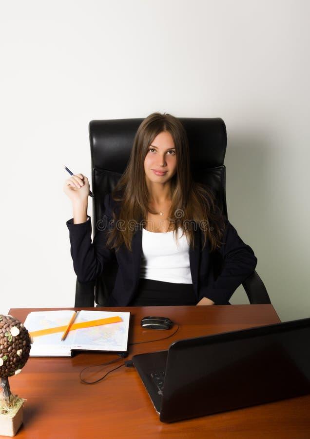 Donna di affari in un vestito che si siede ad uno scrittorio fotografie stock