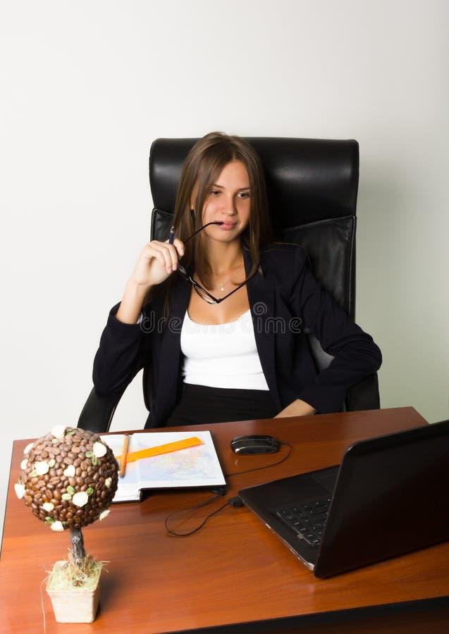 Donna di affari in un vestito che si siede ad uno scrittorio fotografia stock
