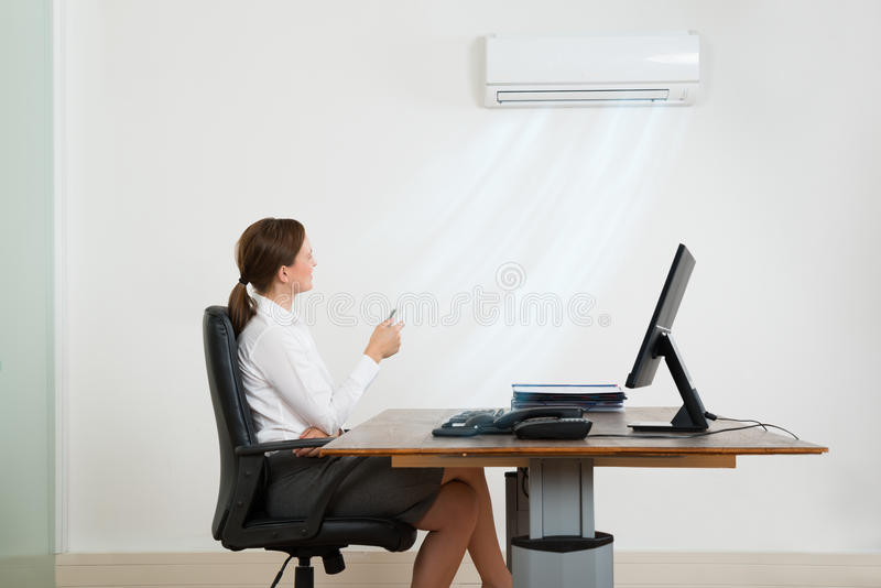 Donna di affari Using Air Conditioner in ufficio immagini stock