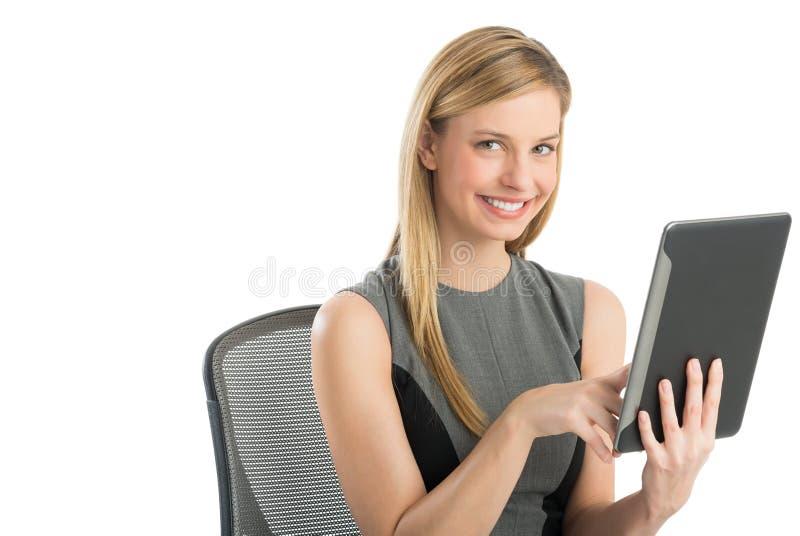 Donna di affari Using Digital Tablet mentre sedendosi sulla sedia fotografia stock