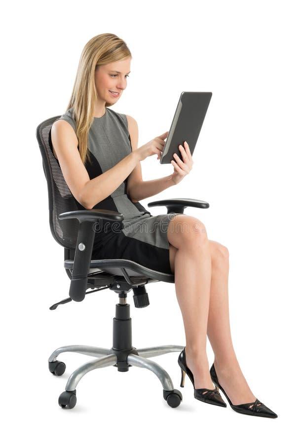 Donna di affari Using Digital Tablet mentre sedendosi sulla sedia dell'ufficio fotografia stock
