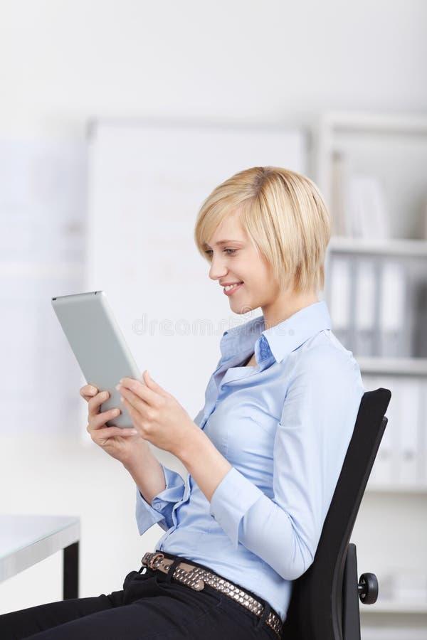 Donna di affari Using Digital Tablet mentre sedendosi sulla sedia dentro fuori immagini stock libere da diritti