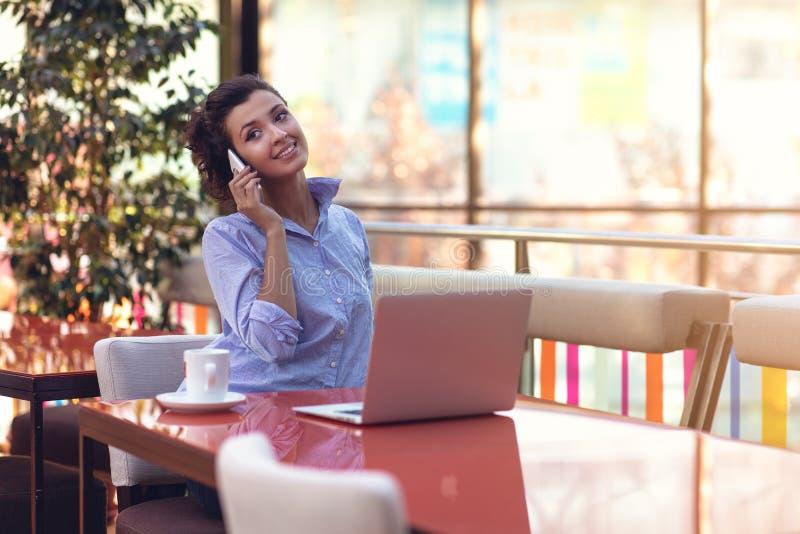 Donna di affari Using Phone While che lavora nella caffetteria fotografia stock